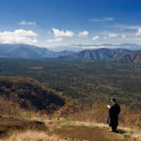 Rites of remembrance: At a point overlooking a section of the 30-sq.-km Aokigahara Jukai forest, Buddhist priest Showzen Yamashita offers prayers for the untold number of people who have entered that 'Sea of Trees' wilderness but failed to make it out alive. | ROB GILHOOLY