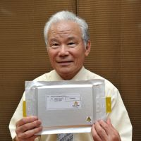 Storage power: Alloy Industry Chairman and founder Yoshinobu Shimoitani holds a lithium-ion battery made by his company during an interview in Tokyo on July 26. | YOSHIAKI MIURA