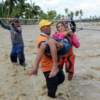 Not the last: A rescue worker carries an elderly resident across a swollen river in New Bataan, Compostela Valley Province, on Thursday, two days after Typhoon Bopha hit. | AFP-JIJI