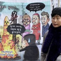 Rocket man: A cartoon caricaturing North Korean leader Kim Jong Un's rocket launch plans is displayed on a Seoul street on Sunday. | THE WORDS AT TOP LEFT READ: 'THE YOUNG PIG (KIM JONG UN) PLAYING WITH FIRE.' AP