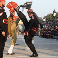 Frontier standoff: Pakistani Rangers (in black) and Indian Border Security Force personnel perform a flag ceremony at the Wagah border crossing Tuesday. Pakistan's army claims Indian troops shot dead one of its soldiers later the same day. | AFP-JIJI