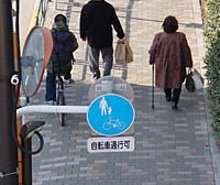 Signs that allow people to bicycle through a sidewalk | ALICE GORDENKER PHOTO
