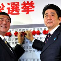 Winning: Liberal Democratic Party Secretary General Shigeru Ishiba (left) and party chief Shinzo Abe place traditional red roses on the names of winning candidates during the Lower House election on Dec. 16. | YOSHIAKI MIURA