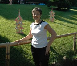 Kazuko Aso, DanDans founder and organizer, stands in front of 'Blooming Pagoda' by Megumi Akiyoshi.