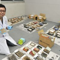 Clean team: Tokyo Metropolitan Museum of Photography curator Keishi Mitsui (above) with some of the 80,000 tsunami-damaged photographic items that are currently being cleaned by volunteers (below) in Tokyo. | YOSHIAKI MIURA
