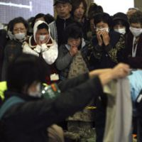 Warm wishes: Evacuees from the radiation zone around TEPCO's Fukushima nuclear power plant wait in the cold at a refuge on March 24 to receive donated clothing. | AP PHOTO
