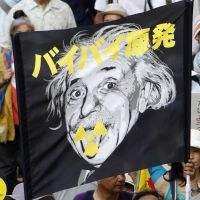 Fear in the air: With the crisis at the Fukushima No. 1 nuclear power plant still ongoing, protesters in a reportedly 60,000-strong anti-nuclear rally in Tokyo on Sept. 19 raise a banner showing Einstein's face overprinted with the slogan 'Bye-bye nuclear power plants,' while the fan below it reads: 'We don't need nuclear power.' | AP PHOTO