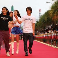 Brave face: Comedy duo Hiking Walking head down the red carpet at the Okinawa International Movie Festival on March 22.