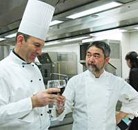 A 'modern' moussaka (free of high-calorie bechamel sauce) was served at the Foreign Correspondents' Club of Japan; the two chefs savor a glass of Greek red wine after a hard day in the kitchen.