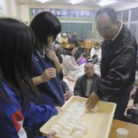 Soul food: Volunteers distribute handmade rice balls at a shelter in Takaharu Town, near Mount Shinmoe in Miyazaki Prefecture, after a volcanic eruption in January this year.