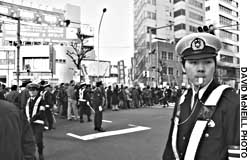 Police stand watch over a march held in Tokyo's Shinjuku Ward earlier this month seeking more rights for foreign workers.