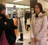 'Personal stylist' Shizuka Inoue (below) gets paid for helping you shop for clothes. Above, she advises one of her clients about the potential purchase of a coat at the Yurakucho Hankyu department store in Yurakucho.   TOMOKO OTAKE PHOTOS