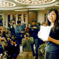 Nanae Aoyama sits before her computer at home (left), where she says she may work on a story for a few hours each night -- or sometimes just for 10 minutes after getting back from the office and meeting friends. The author poses for the Press in Tokyo (right) holding the magazine in which her Akutagawa Prize-winning story was first published, after her award was announced in January. | PHOTO COURTESY OF NANAE AOYAMA; KYODO PHOTO