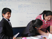 In a fourth-grade math class at Global Indian International School, students line up to show their answers to the teacher.
