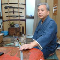 Beauty consultant: Sword-polisher Yoshihiko Usuki at work in his home-workshop in downtown Tokyo. 'If the only role of a sword was to cut things, there would be no need to polish it to make it shiny,' he says. | YOSHIAKI MIURA PHOTO