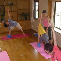 Hands on: Linda Gould helps her students through their poses in her Riverside Yoga studio. Gould, who teaches daily until midday, teaches Hatha yoga, 'which connects controlled movement with controlled breathing.'