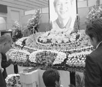 Floral tribute: Rows of flowers are neatly arranged to decorate the altar with the picture of the deceased. | SATOKO KAWSAKI PHOTO