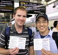 Into the storm: Corey Pederson (left) and Mike Kim disembark in Tokyo (top), the halfway point in their attempt to break the Guinness world record for the furthest distance traveled by train in 24 hours, and displaying their overworked JR rail passes (above) before setting off on the fateful Kyushu-bound leg of their journey (below) during which deluges swamped their record attempt (bottom).   YOSHIAKI MIURA PHOTO; EDAN CORKILL (bottom)