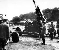 In the clear: Emperor Michinomiya Hirohito, who never had to face the Tokyo Trial, is seen (third from right) inspecting anti-aircraft guns in Tokyo on June 8, 1942. | AP PHOTO