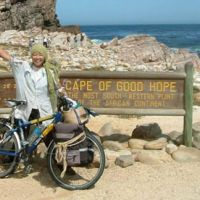 Endings, new beginnings: Mio Yamasaki waves in triumph in 2005 at the endpoint of her bicycle tour — the Cape of Good Hope. | COURTESY OF MIO YAMASAKI