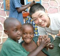 Taking off: An intentionally boyish-looking Mio Yamasaki poses with two youngsters outside the barbershop just after getting her head shaved in Africa in 2004. Yamasaki then set out on a bicycle tour that would last six months and cover 5,000 km winding through the African continent. | COURTESY OF MIO YAMASAKI