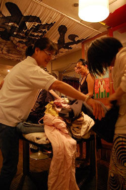 Swap shop: Women hold clothes against themselves to check the size at the charity clothes swap last month in Tokyo's Shibuya. The event at the bar/cafe The Pink Cow is held regularly throughout the year. A door fee goes to charity, as does any leftover clothing. In addition to clothing, shoes, belts, bags and other accessories are to be found among the treasures.