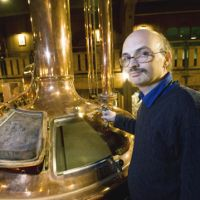 Johannes Braun, brewmeister at Otaru Beer, poses next to a copper brewhouse he brought over with him from Germany at Soko No. 1, the brewery-cum-beer hall he runs in Otaru, Hokkaido. | ROB GILHOOLY PHOTOS