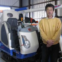 Duty bound: Atsuo Aoki stands next to the combine he's bought for the family's small rice farm he feels it's his filial duty to maintain whatever the cost.
