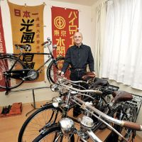 On your bike: Eric Ossing, a collector and restorer of classic Japanese bicycles, is seen here in his home workshop in Kawasaki that's hung with old bike ads. | YOSHIAKI MIURA PHOTO