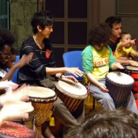 Bang it slowly: Participants in the last 'Rhythm and Hope' event organized by Refugee International Japan in June 2009 in Tokyo join in an African drum session. | COURTESY OF RIJ