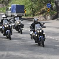 Peter Verbisen (left), Johan Cole (center) and Carl Tricke pose on a street in Almaty, Kazakhstan, on April 30 during their 83-day motorcycle tour from Antwerp to Tokyo.