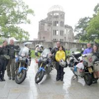 The three men are joined by their wives for a group photo in front of the Hiroshima Peace Memorial on June 26.