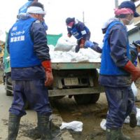 Partners in peace?: A Peace Boat volunteer crew sent to Ishinomaki, Miyagi Prefecture, by IBM Corp. clears mud and debris from a residence. | DREUX RICHARD