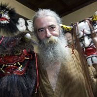 Jake Davies holds two of his Iwami-Kagura masks — the female demon Hannya (right) and the Akaoni (red demon) —  at his home in the small town of Sakurae in Shimane Prefecture. | ROB GILHOOLY PHOTOS