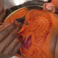 Touch up: A theyyam dancer's face is painted with traditional patterns.