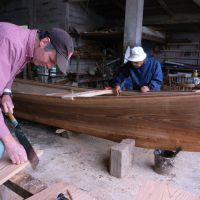 Douglas Brooks works with Ryujin Shimojo to build a sabani in December 2009 as the American boat builder chronicles the craft of building a traditional, wooden Okinawa fishing boat. Below: Brooks sits in front of Shimojo's workshop on Iejima Island, Okinawa Prefecture. | PHOTOS COURTESY OF DOUGLAS BROOKS, MICK CORLISS
