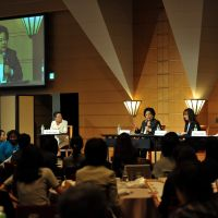 Merle Aiko Okawara, chairman of JC Comsa Corp., is shown on the screen as she makes a presentation at a symposium on leadership and diversity held Oct. 28 in Tokyo, while moderator Kimiko Horii (left), president of Research Institute of Self-Esteem, Leslie Grossman (second from right), president of Leslie Grossman Leadership, and Tetsuya Ando, founder of the nonprofit organization Fathering Japan, look on. | YOSHIAKI MIURA PHOTO