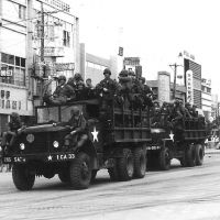 Two trucks carrying U.S. servicemen pass by on a street in what was then Koza.