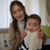 The written word: Michiko Torii, a stay-at-home mom in Tokyo's Minato Ward, poses with her 5-month-old son, Keisuke. In the background is a framed calligraphy rendering of his kanji name preceded by two small characters above it that are a traditional, formal way of saying: 'Let the name be.' The writing down the side records the baby's birthday. Japanese parents often have artworks like this made of their children's names to put on display in the home, where they pray to them for their healthy development. | TOMOKO OTAKE
