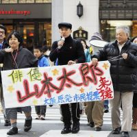 Taro Yamamoto on the streets campaigning for a nuclear power-free Japan in Koriyama, Fukushima Prefecture in October 2011; in Osaka in December 2011. | KYODO