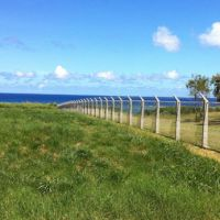 Keep out: A fence topped with razor-wire separates the U.S. Iejima Island Auxiliary Airfield (right) from Japan.   JON MITCHELL