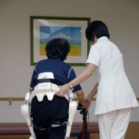 All together now: A nurse and a 'HAL for Wellbeing' assist a patient during ongoing trials of the robot suit in Japan.   YOSHIYUKI SANKAI, UNIVERSITY OF TSUKUBA / CYBERDYNE INC.