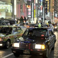 Fare game: Lines of modern-day taxis wait for customers in Tokyo's posh Ginza shopping district.   YOSHIAKI MIURA