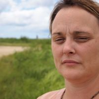 Directly affected: Second-generation Agent Orange survivor Heather Bowser, who visited Okinawa in late August, is interviewed at a location overlooking U.S. Marine Corps Air Station Futenma in Ginowan.   JON MITCHELL