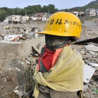 Man for the moment: A statue of Jizo, protector of children and travelers, stands at a roadside in the town of Onagawa, Miyagi Prefecture, three months after the March 11, 2011, disasters. A message on his helmet reads 'Thank you, everyone.' | KYODO