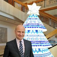 Seasonal cheer: Ambassador Jari Gustafsson stands in front of a display in the foyer of the Finnish Embassy in Tokyo's Shibuya Ward recently. The Christmas tree in the background — a combination of Nagoya 'chochin' (Japanese-style lantern) and Finnish patterns — was designed by Mai Ohta, a Japanese designer at Finnish textile and clothing company Marimekko. | YOSHIAKI MIURA