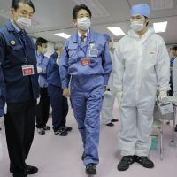Going nuclear again?: Prime Minister Shinzo Abe (center) inspects Tokyo Electric Power Co.'s emergency operation center at the crippled Fukushima No. 1 nuclear power plant in Okuma, Fukushima Prefecture, on Dec. 29. His ruling Liberal Democratic Party has pledged to review the previous Democratic Party of Japan government's plans to phase out nuclear power. | AP