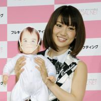 AKB48's Yuko Oshima holds a doll at a press conference for an Internet Service Provider, which features a computer program that lets fans see what a baby between them and their favorite member of AKB48 might look like.   KYODO
