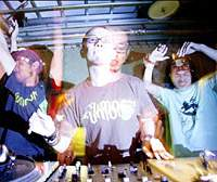 Kai Ishikawa (center), DJ and organizer of the 'SOLID' events at La Fabrique, mans the decks flanked by two partygoers. | RYU KASAI PHOTO