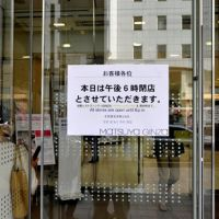 Lights out: A sign on the door of Matsuya Ginza department store lets shoppers know that it is closing at 6 p.m., two hours earlier than usual. To conserve energy, many Tokyo businesses are changing opening hours or closing altogether until further notice. | YOSHIAKI MIURA PHOTO